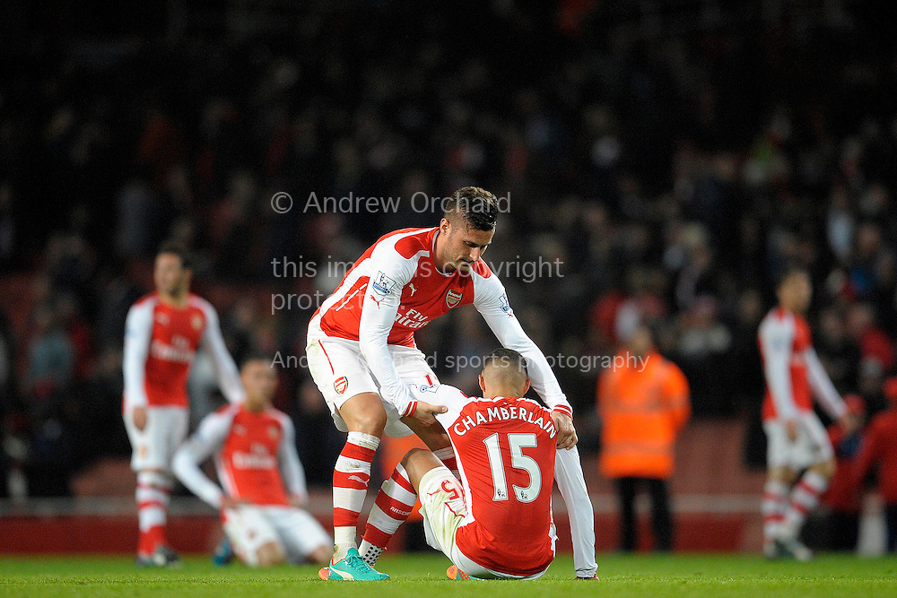 a dejected Olivier Giroud of Arsenal helps up Alex Oxlade-Chamberlain of Arsenal after the final whistle. Barclays Premier league match, Arsenal v Manchester Utd at the Emirates Stadium in London on Saturday 22nd November 2014.<br /> pic by John Patrick Fletcher, Andrew Orchard sports photography.