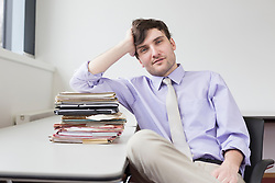Portrait of businessman sitting in office with stack of files