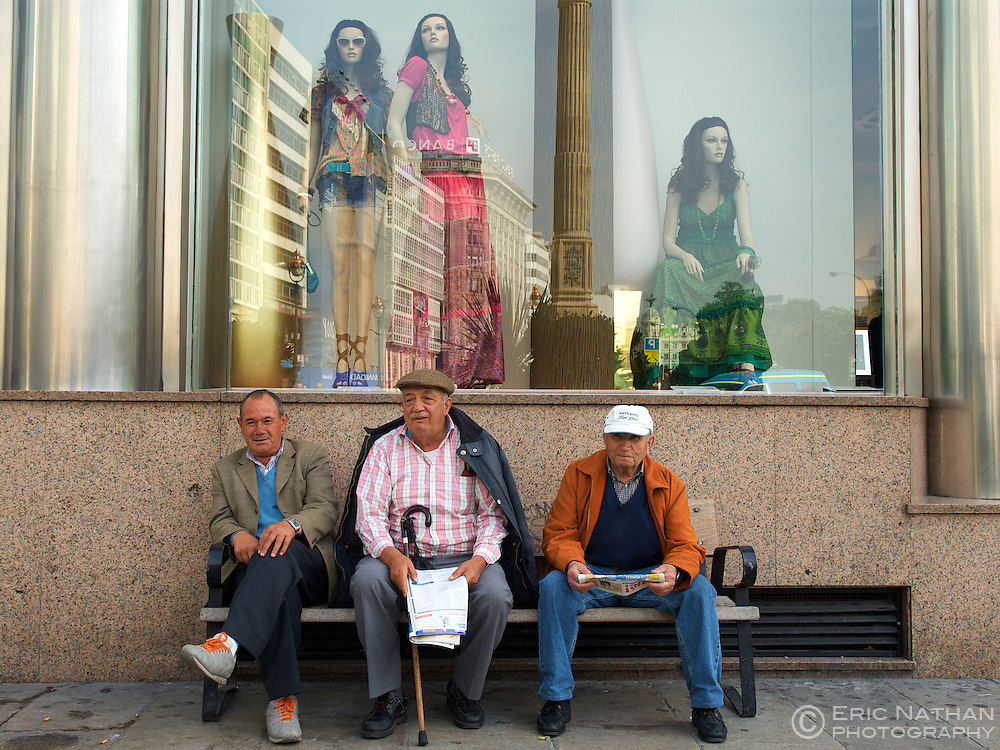 Three Spanish men sitting on a bench in the town of La Coruna in the Galicia region of Spain.