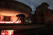 """A person places candles at  a makeshift memorial in Berlin, Germany, January 17,  2021. The memorial is part of the initiative  """"Corona-Tote sichtbar machen"""" (lit. Make corona deaths visible) by Christian Y. Schmidt and Veronika Radulovic,  since December 6, 2020, people gather at the fountain of Arnswalder Platz every Sunday at 16:00, light candles and place placards with the current death toll reported in Germany at the time. The death toll in Germany by variouse sources revolved around 47,000."""