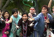 2/7/04--GASPARILLA--It's all about the beads. From left,  Ploi Phayoungsin,  (white shirt blue boa) Oratip Jitvivatporn (brown) and Liz Tipton (blue) grab for beads thrown in their direction along the parade route. Michael Spooneybarger/Tampa Tribune photo.