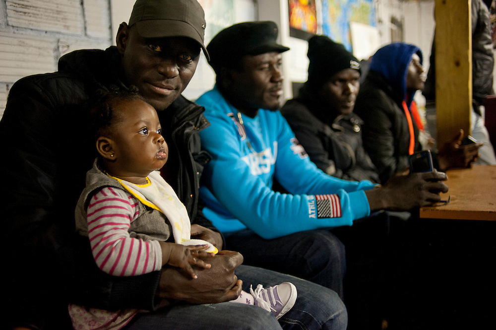 Afrikaanse migranten in gemeenschappelijke huiskamer. Sinds 2011 wonen 150 Afrikaanse migranten in een voormalige fabriek in de Parijse voorstand Montreuil, omdat ze illegaal in Frankrijk verblijven, kunnen ze geen woonruimte huren. In het 450 m2 grote pand wonen jonge mannen uit Malië, Ivoorkust, Bukina Faso, Niger.