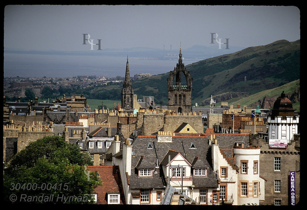 Rooftops and smokestacks of old buildings frame Firth of Forth in distance; Edinburgh. Scotland