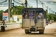 16 JUNE 2014 -  A Thai immigration police truck takes Cambodian migrants back to Cambodia through Aranyaprathet, Thailand. More than 150,000 Cambodian migrant workers and their families have left Thailand since June 12. The exodus started when rumors circulated in the Cambodian migrant community that the Thai junta was going to crack down on undocumented workers. About 40,000 Cambodians were expected to return to Cambodia today. The mass exodus has stressed resources on both sides of the Thai/Cambodian border. The Cambodian town of Poipet has been over run with returning migrants. On the Thai side, in Aranyaprathet, the bus and train station has been flooded with Cambodians taking all of their possessions back to Cambodia.PHOTO BY JACK KURTZ