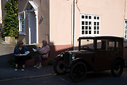 Women eat their chips beside vintage cars on show at the annual Michaelmas Fair in the small market town of Bishops Castle, England, United Kingdom.