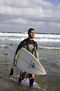 A surfer emerges from the ocean, Tel Aviv, Israel
