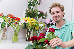 Mid adult man holding red rose, smiling
