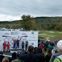 SunTrust Racing Chevrolet Corvette DP drivers Max Angelelli and Ricky Taylor (left and right in yellow hats, top step) on the podium following their victory in the Grand-Am Rolex Sports Car Series Championship Race at Lime Rock Park in Lakeville, Conn.
