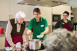 Nursing staff assisting senior woman cooking in rest home