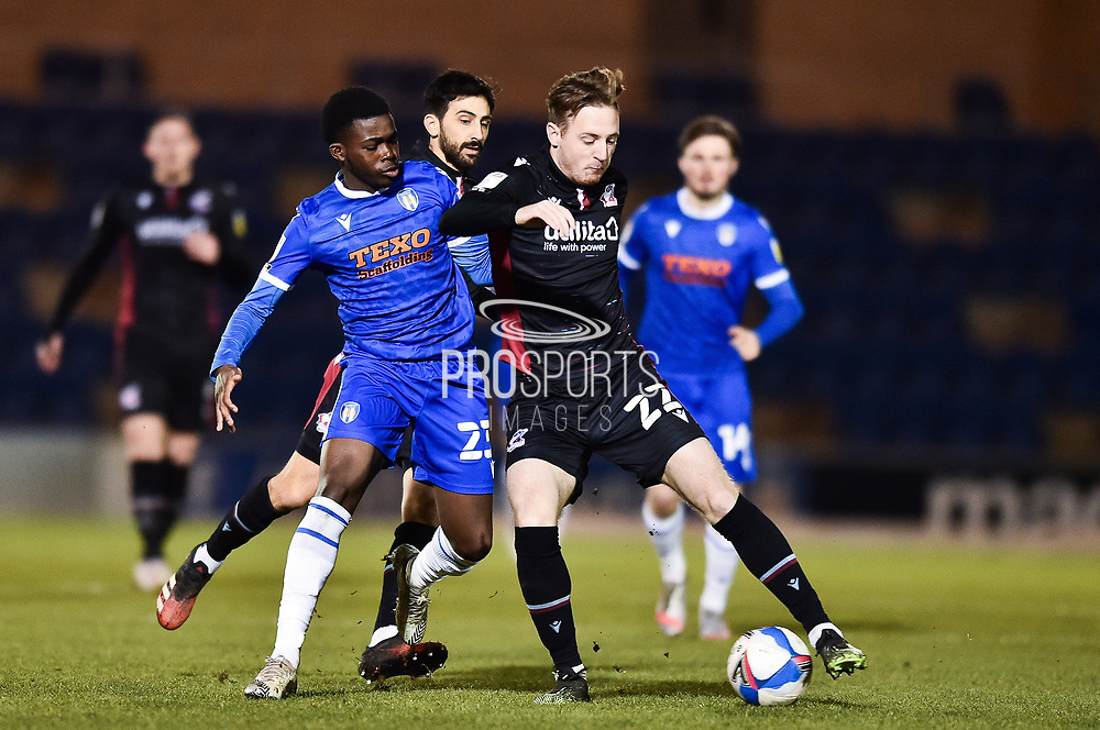 Alfie Beestin (22) of Scunthorpe United  battles for possession with Colchester United's Kwame Poku (23) during the EFL Sky Bet League 2 match between Colchester United and Scunthorpe United at the JobServe Community Stadium, Colchester, England on 29 January 2021.