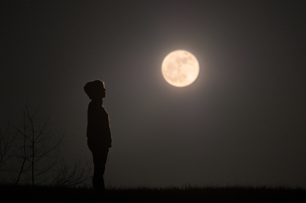 A profile view of a girl wearing a hoodie stands silhouetted surrounded by darkness under a full moon looking to be lost in thought.