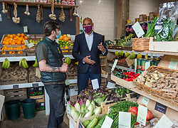 """© Licensed to London News Pictures; 24/05/2021; Bristol, UK. Bristol's elected Mayor MARVIN REES, looks at fruit and veg with OLI from Hugo's Greengrocer at The Bristol Loaf on Bedminster Parade. The mayor met shoppers and traders in Bedminster to launch """"Where's it To?"""", a new high street support campaign by Bristol City Council. Where's it to? is an invitation to Bristolians to explore their local high streets, shop local and get to know the traders behind the businesses. 15 high streets across the city will be profiled, highlighting numerous traders on each street, which span from stores passed through generations of a family, through to brand new openings inspired by the covid coronavirus pandemic. The phrase """"Where's it to?"""" is what Bristolians traditionally say meaning 'where is that?' and  was selected as the name of the campaign to reflect the city's language and in collaboration with a huge range of traders from across the 15 high streets. Photo credit: Simon Chapman/LNP."""