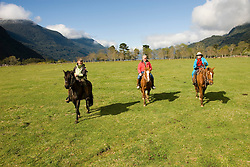 Chile, Lake Country: People riding horses at Peulla in a meadow in the Andes..Photo #: ch607-33251..Photo copyright Lee Foster www.fostertravel.com, lee@fostertravel.com, 510-549-2202.
