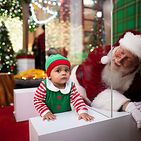 WILLOW GROVE, PA:  Jeseph Alvarez, 10 months, reacts while meeting John Byers, 63, in his 7the year as Santa, separated through plexiglass due to the coronavirus (COVID-19) pandemic, at the Willow Grove Park Mall in Willow Grove, PA on December 7, 2020.  The pandemic has forced difficult decisions about maintaining the holiday tradition of visits to Santa Claus versus safety concerns.  Plexiglass dividers, face shields, and physical distancing are among the precautions for those locations that have proceeded with Santa photo opportunities.  CREDIT:  Mark Makela for The New York Times
