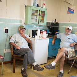 "August 4, 2017 - Tangier Island, VA - <br /> Inside the ""Situation Room,""  (named after a small briefing room in the White House) is a small room inside the former Tangier Island health clinic, where watermen gather at the end of the day to ""solve all the world's problems,"" according to Tangier Island Mayor James ""Ooker"" Eskridge (not pictured). From left to right, Leon McMann (the mayor's father-in-law) and George Cannon are part of the daily gathering in this close-knit island community  Photo by Susana Raab/Institute"