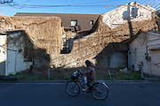 A woman rides a bicycle past an over-grown derelict house in Shinjuku, Tokyo, Japan, Thursday February 27th 2020