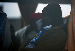 © Licensed to London News Pictures. 24/10/2016. Calais, France. A migrant wearing a LEICESTER CITY FOOTBALL CLUB scarf, on board the first bus to leave the camp as the evacuation and demolition begins at the migrant camp in Calais, known as the 'Jungle'. French authorities have given an eviction order to thousands of refugees and migrants living at the makeshift living area of the French coast. Photo credit: Ben Cawthra/LNP