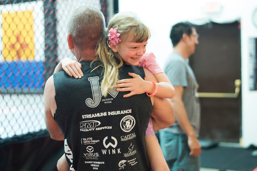 Coach Mike Winkeljohn lifts his daughter in the air at Jackson Wink MMA in Albuquerque, New Mexico on June 10, 2016.