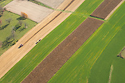 Aerial photograph of corn harvest with a combine, tractor and wagon in rural Wisconsin.