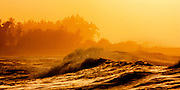 Sunset ridges of trees and giant winter surf on Oahu's North Shore at Turtle Bay, Hawaii