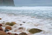 ocean waves washing across rocks on beach