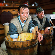 Shepherds make cheese in a wooden bucket whilst smoking a cigarette, Lunca Ilvei, Romania