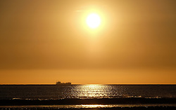 © Licensed to London News Pictures.12/06/15<br /> Saltburn by the Sea, England<br /> <br /> A container ship is seen on the horizon as the morning sun climbs over Saltburn by the Sea.<br /> <br /> Photo credit : Ian Forsyth/LNP