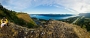 A panoramic image of a photographer taking photos of the Columbia River Gorge from a ridgle that  overlooks the Columbia River and Vista House in Corbett, Oregon.