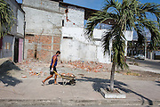 2016/10/10 – Bahia de de Caráquez, Ecuador: A man carries wreckage of the house he is rebuilding in Bahia de Caráquez, Ecuador, 10th October 2016. Many people don't believe they will get any Government help, so they have started to rebuild their houses by themselves. (Eduardo Leal)