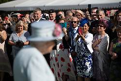 Guests take photos of Queen Elizabeth II during the Royal Garden Party at Buckingham Palace in London.