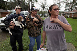 30 August 2012. Laplace, Louisiana,  USA. .R/L; Maria Keating weeps as she is forced to evacuate her home in Laplace with her husband Carl, son Andrew and their dogs as flood waters continue to rise. Flooding forced the emergency evacuation of hundreds of homes  when waters rose suddenly in the early morning hours as hurricane Isaac lingered over southern Louisiana. .Photo; Charlie Varley.