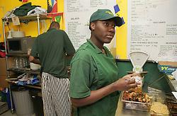 Staff working in Caribbean café taking orders and preparing food,