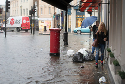 © Licensed to London News Pictures. 25/07/2021. London, UK. Members of the public attempt to stay dry as they walk past a section of flooded road in Greenwich Town Centre in South East London . An amber weather warning for thunderstorms is in place in parts of London and the South East . Photo credit: George Cracknell Wright/LNP