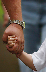 A father clasps his son's hand outside St Andrew's Church, Soham, Cambridgeshire after a special church service to give prayers for missing schoolgirls Holly Wells and Jessica Chapman. It is believed they were abducted and murdered.