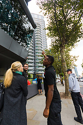 Bystanders point to where a missing window can be seen at the top of the building as a police cordon surrounding a forensics tent remains in place outside The Corniche on the Albert Embankment in London after a window pane fell yesterday morning killing passing coach driver Mick Ferris. Albert Embankment, London, October 03 2018.