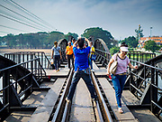 "09 JANUARY 2019 - KANCHANABURI, THAILAND: People take pictures on the ""Bridge On the River Kwai"" in Kanchanaburi, Thailand. Hundreds of thousands of Asian slave laborers and Allied prisoners of war died in World War II constructing the ""Death Railway"" between Bangkok and Rangoon (now Yangon), Burma (now Myanmar) for the Japanese during World War II.  The bridge is now one of the most famous tourist attractions in Thailand.       PHOTO BY JACK KURTZ"