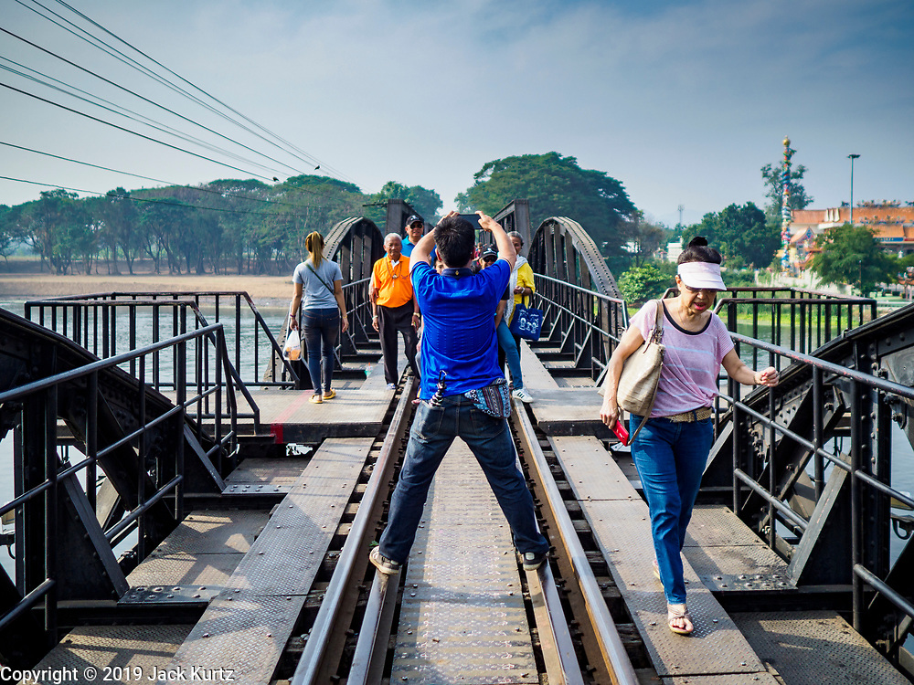 """09 JANUARY 2019 - KANCHANABURI, THAILAND: People take pictures on the """"Bridge On the River Kwai"""" in Kanchanaburi, Thailand. Hundreds of thousands of Asian slave laborers and Allied prisoners of war died in World War II constructing the """"Death Railway"""" between Bangkok and Rangoon (now Yangon), Burma (now Myanmar) for the Japanese during World War II.  The bridge is now one of the most famous tourist attractions in Thailand.       PHOTO BY JACK KURTZ"""