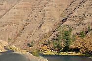 A winding road follows the bank of the Grande Ronde River, Asotin County, WA, USA  Autumn colors the canyon deciduous foliage.