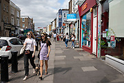 Fashionable young women, one with her small dog walking along Portobello Road in West London, England, United Kingdom.