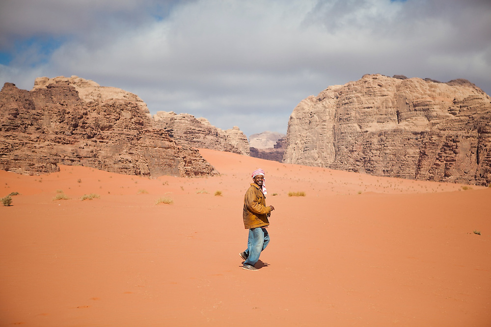 Sudanese Bedouin driver Ahmed jogs across the sand for fun in Wadi Rum, Jordan.
