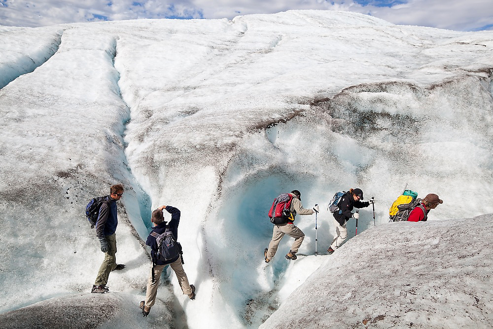 Clients are led by guide Ben Wilcox up a meltwater canyon on a day trip on the Root Glacier in Wrangell-St. Elias National Park, Alaska.