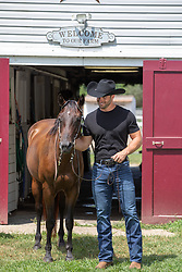 sexy cowboy with a horse by a barn