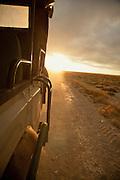 A Land Rover drives through Amboseli National Park at dawn, Kenya
