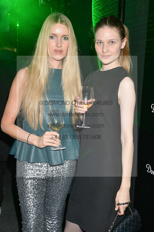 Left to right, ANNA BUDEL and LARISA KLITSINARI at a reception to celebrate Dom Perignon and Iris van Herpen's collaboration 'Metamorphosis' held at the Hus Gallery, 10 Hanover Street, London on 27th October 2014.
