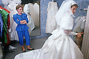 A bride-to-be tries on her white wedding dress during a fitting in a London bridal shop. Watched by a family friend or relative, the lady about to be married gives a thumbs up to unseen people as if to say she likes the garment and will be buying it for her special day. The friend however looks sceptical and stand in a defiant, disapproving stance, with arms folded and a doubtful look on her face. More dresses hang on rails in the background so there is more choice but it seems this bride is having her own way.