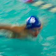 A young swimmer at a YMCA pool shows off his butterfly stroke.