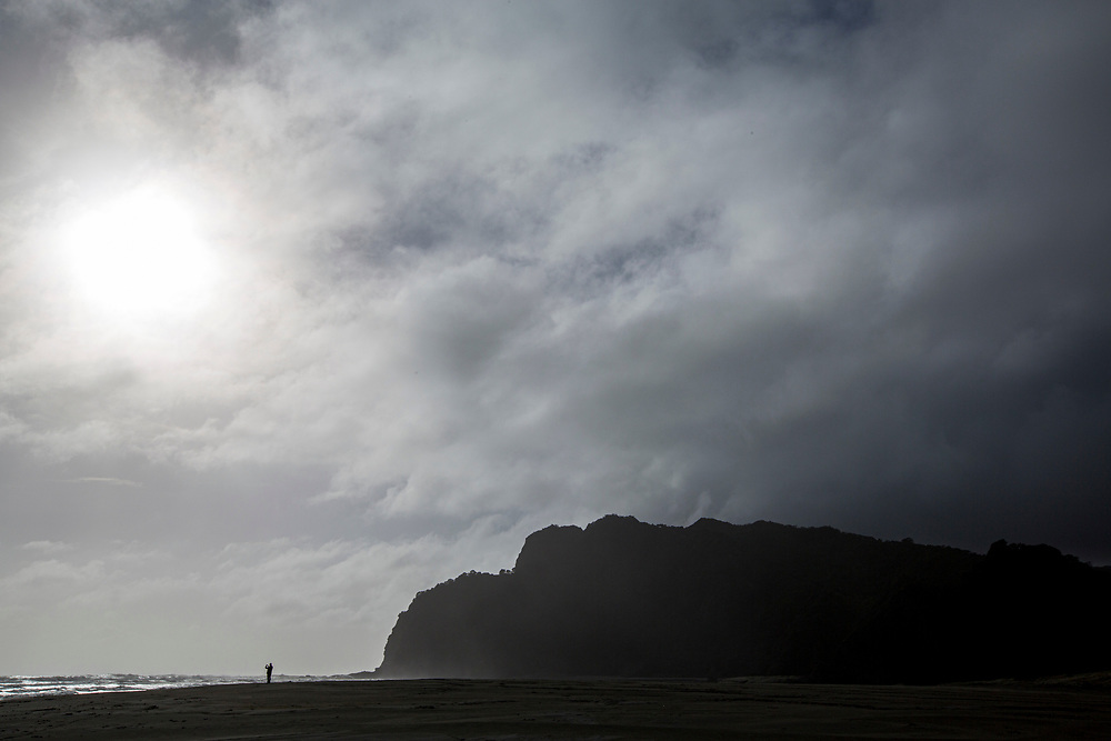 Famous North Island west coast beach where the Jane Campion movie The Piano was shot showing moody skies with distant people.