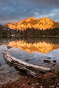 Orange sunrise light strikes Sawtooth Wilderness mountains reflected in Pettit Lake, near Stanley, Idaho, in Sawtooth National Recreation Area, USA. The Sawtooth Range (part of the Rocky Mountains) are made of pink granite of the 50 million year old Sawtooth batholith. Sawtooth Wilderness, managed by the US Forest Service within Sawtooth National Recreation Area, has some of the best air quality in the lower 48 states (says the US EPA).