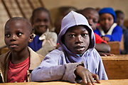 Children studying at their desks in the class 3 school room. The school consists of 6 teachers with approximately 60 children in each class.  Undugu Society of Kenya (USK) are an NGO who run various programmes to help the school and pupils including a lunchtime feeding program.