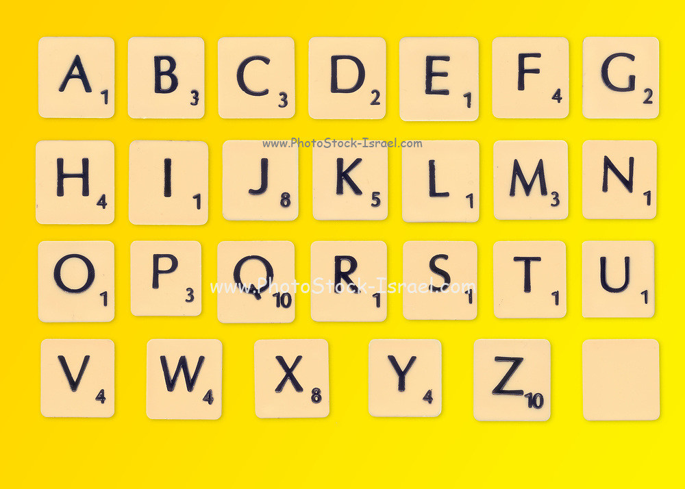 Digitally created image of a full alphabet of scrabble tiles on a yellow background
